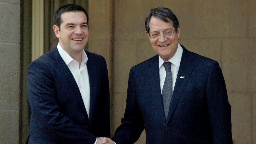 Greek Prime Minister Alexis Tsipras, left, and Cyprus' President Nicos Anastasiades shake hands at the presidential palace before a meeting in capital Nicosia, Cyprus Wednesday, April, 29, 2015. Anastasiades and Tsipras are joined by Egyptian President Abdel-Fattah el-Sissi for a summit meeting on the east Mediterranean island to discuss ways of tighter economic and security cooperation between the three countries. The leaders will also discuss unfolding developments in neighboring countries including Yemen, Libya, Syria and Iraq. The meeting follows an initial summit that took place last November in Cairo, Egypt. (AP Photo/Petros Karadjias)