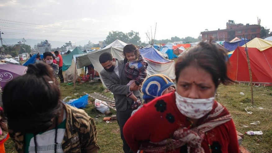 Nepalese people prepare to go back home after sleeping on open grounds for four nights to be safe from earthquake in Kathmandu, Nepal, Wednesday, April 29, 2015. Thousands of people are lining up at bus stations in Kathmandu where the government is providing free transportation for people hoping to travel to their hometowns and villages. The government has even deployed school buses to supplement the overstretched service. (AP Photo/Niranjan Shrestha)
