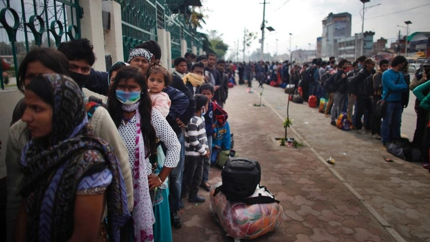 Nepalese people line up to board buses go to their villages in Kathmandu, Nepal, Wednesday, April 29, 2015. Thousands of people are lining up at bus stations in Kathmandu where the government is providing free transportation for people hoping to travel to their hometowns and villages. The government has even deployed school buses to supplement the overstretched service. (AP Photo/Niranjan Shrestha)