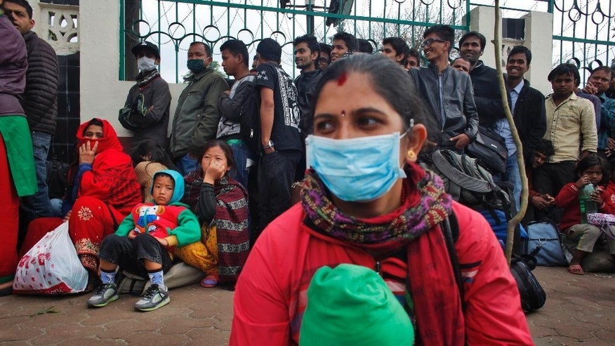 Nepalese people wait to board buses go to their villages in Kathmandu, Nepal, Wednesday, April 29, 2015. Thousands of people are lining up at bus stations in Kathmandu where the government is providing free transportation for people hoping to travel to their hometowns and villages. The government has even deployed school buses to supplement the overstretched service. (AP Photo/Niranjan Shrestha)