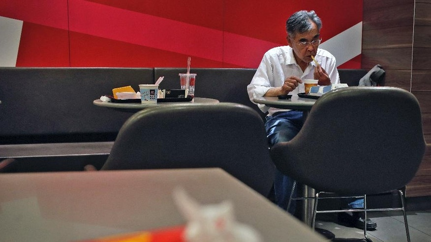 A man eats french fries at a McDonald's restaurant in Beijing, China Thursday, April 30, 2015. A french fry supplier to the McDonald's restaurant chain in China has been issued Beijing's biggest-ever pollution fine for releasing dirty wastewater, state media reported. (AP Photo/Andy Wong)