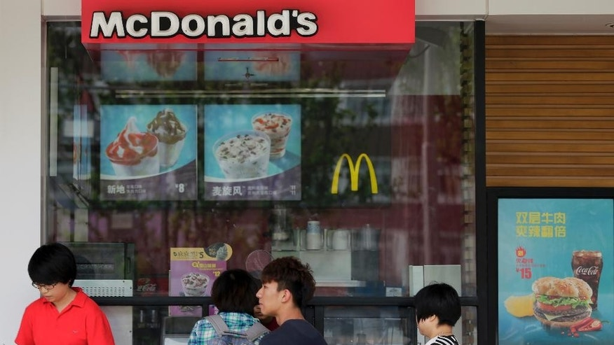 Chinese people buy sundae cones at a McDonald's restaurant in Beijing, China, Thursday, April 30, 2015. A french fry supplier to the McDonald's restaurant chain in China has been issued Beijing's biggest-ever pollution fine for releasing dirty wastewater, state media reported. (AP Photo/Andy Wong)