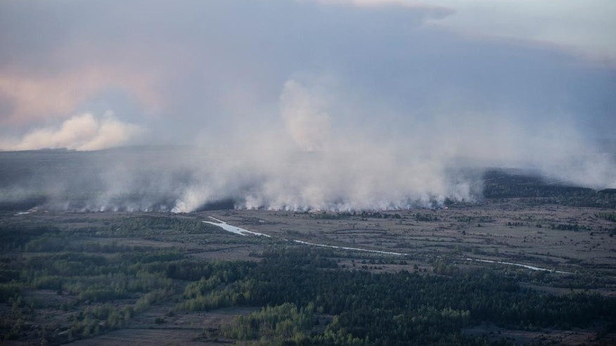 An aerial view of a forest fire in the Chernobyl area, Ukraine, Tuesday, April 28, 2015. Fire has engulfed a large sector of woods in the exclusion zone around the destroyed Chernobyl nuclear power plant. Ukrainian prime minister Arseniy Yatsenyuk says the fire is being brought under control. (AP Photo/Andrew Kravchenko, Pool)