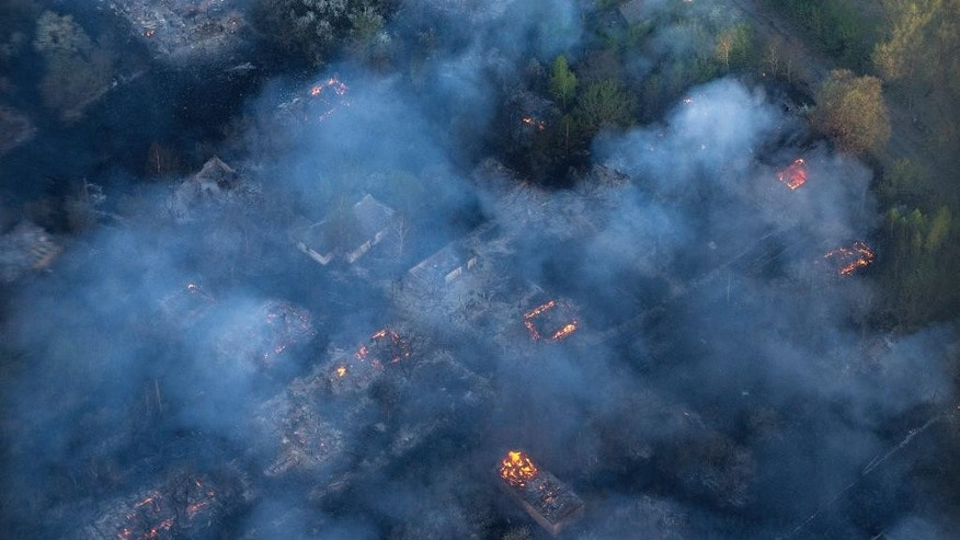 Fire hits an abandoned village in the exclusion zone around Chernobyl, Ukraine, Tuesday, April 28, 2015, as fire has engulfed a large sector of woods in the exclusion zone around the destroyed Chernobyl nuclear power plant. Ukrainian Prime Minister Arseniy Yatsenyuk says the fire is being brought under control. (AP Photo/Andrew Kravchenko, Pool)