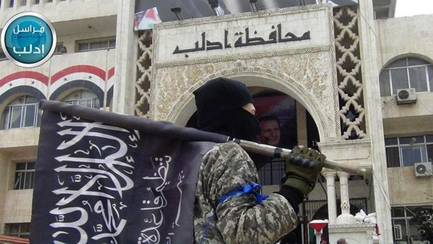 FILE - In this file photo posted on the Twitter page of Syria's al-Qaida-linked Nusra Front on Saturday, March 28, 2015, which is consistent with AP reporting, a fighter from Syria's al-Qaida-linked Nusra Front holds his group flag as he stands in front of the governor building in Idlib province, north Syria. In the span of a month, a coalition of Syrian insurgents has routed government forces across the country's northwest, flushing them out of strongholds in a string of embarrassing loses for President Bashar Assad. (Al-Nusra Front Twitter page via AP, File)