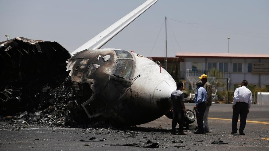 April 29, 2015: Officials of Felix Airways, a domestic airline, inspect a plane destroyed by Saudi-led airstrikes, at the Sanaa International airport, in Yemen.