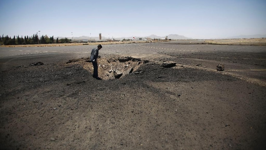 April 29, 2015: A Yemeni man looks at a crater, at the Sanaa International airport, in Yemen.