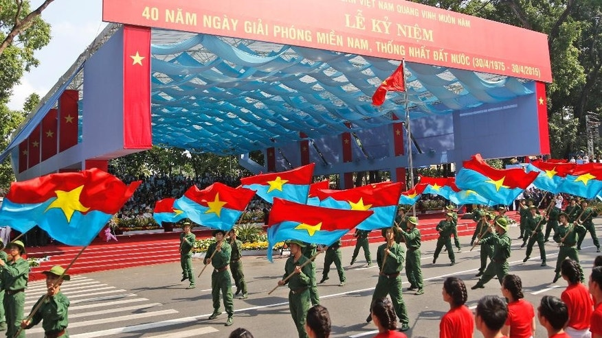 """Performers wave the National Liberation Front flags during a parade celebrating the 40th anniversary of the end of the Vietnam War which is also remembered as the """"fall of Saigon,"""" in Ho Chi Minh City, Vietnam, Thursday, April 30, 2015. (AP Photo/Dita Alangkara)"""
