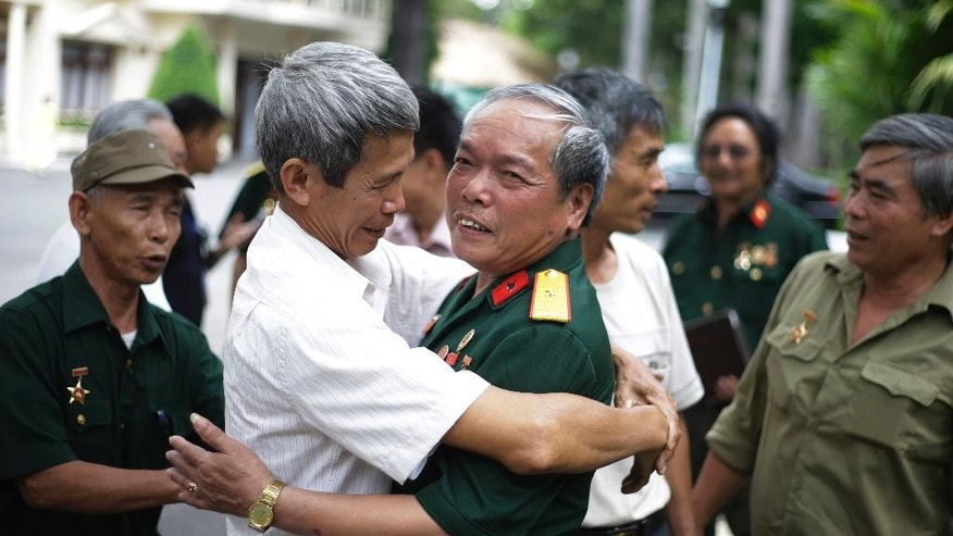 Vietnamese veteran, Nguyen Van Tap, center right, who drove the tank that crashed through the gate of the presidential palace in Saigon in 1975, is embraced by a friend who served along with him in the same tank company, during their reunion ahead of the commemoration of the 40th anniversary of the end of the Vietnam War in Ho Chi Minh City, Vietnam, Wednesday, April 29, 2015. The city, formerly known as Saigon, is set to celebrate anniversary on April 30. (AP Photo/Dita Alangkara)