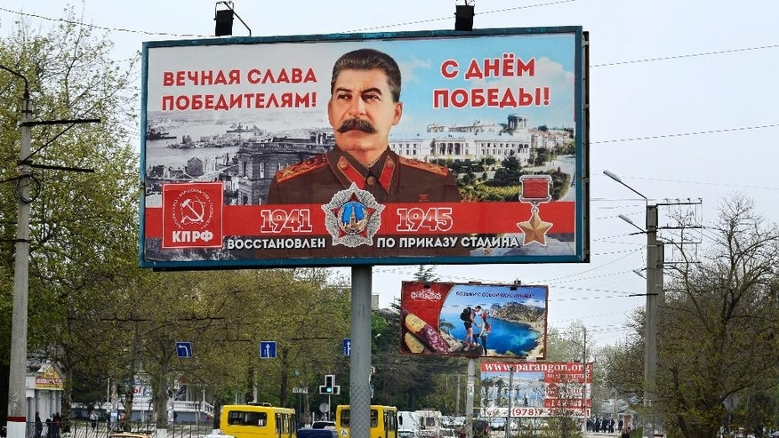 "A billboard reading ""Eternal glory to the victors""  sponsored by the Communist Party, which has always praised Stalin's role in the defeat of Nazi Germany is seen in a street in Sevastopol, Thursday, April 30, 2015. Billboards with the image of Soviet dictator Josef Stalin have appeared all over Sevastopol in Russian-annexed Crimea in the run-up to Victory Day celebrations on May 9.(AP Photo/Anton Volk)"