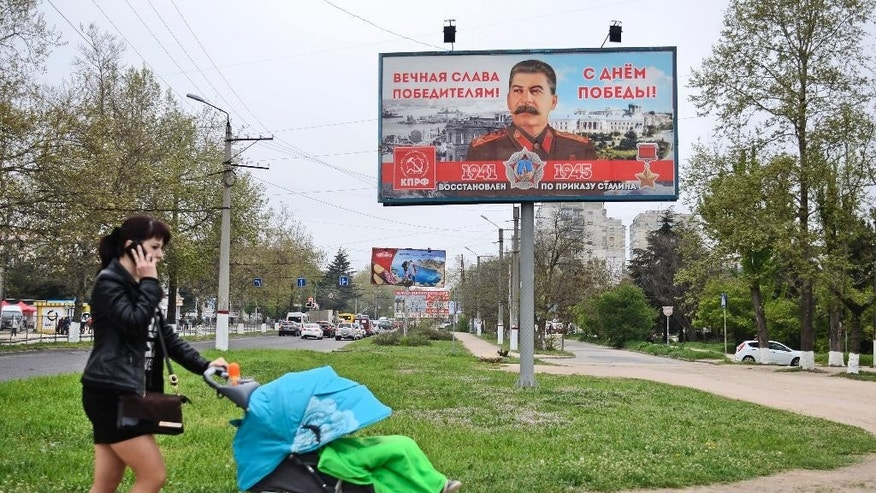 "A woman pushes her baby in front of a billboard reading ""Eternal glory to the victors""  sponsored by the Communist Party, which has always praised Stalin's role in the defeat of Nazi Germany is seen in a street in Sevastopol, Crimea, Thursday, April 30, 2015. Billboards with the image of Soviet dictator Josef Stalin have appeared all over Sevastopol in Russian-annexed Crimea in the run-up to Victory Day celebrations on May 9.(AP Photo/Anton Volk)"
