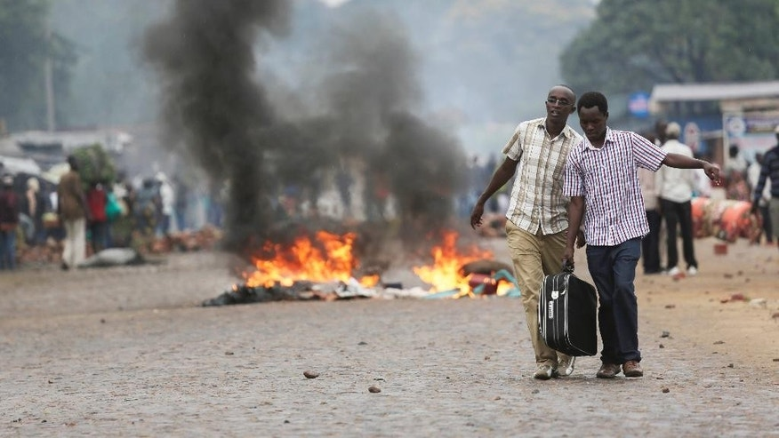 Two men carry a suitcase past a burning barricade in Bujumbura, Burundi Thursday, April 30, 2015, after the government issued and ordered for all university campuses to close down. Bujumbura has been hit by street protests since Sunday as the security forces confront demonstrators who say a third term for President Pierre Nkurunziza would violate the country's constitution. (AP Photo/Jerome Delay)