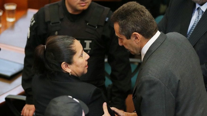 Chief of staff during the government of Colombia's former President Alvaro Uribe, Bernardo Moreno, right, talks to Maria del Pilar Hurtado, former head of Colombia's domestic intelligence agency, as they arrive to the Supreme Court in Bogota, Colombia, Thursday, April 30, 2015. Hurtado was sentenced to 14 years in prison for a scandal prompted by revelations that the agency she headed in 2007-2008 spied on judges, journalists, and rights activists opposed to then-President Uribe. Moreno was sentence to eight years for conspiracy and abuse of power charges, for his alleged role in a domestic spying scandal. (AP Photo/Fernando Vergara)