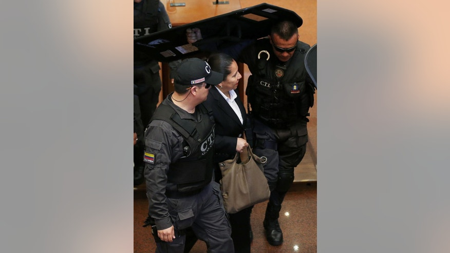 Maria del Pilar Hurtado, right, former head of Colombia's domestic intelligence agency, is escorted by judicial police into the Colombian Supreme Court to receive her sentence, in Bogota, Colombia, Thursday, April 30, 2015. Hurtado was sentenced to 14 years in prison for a scandal prompted by revelations that the agency she headed in 2007-2008 spied on judges, journalists, and rights activists opposed to then-President Alvaro Uribe. (AP Photo/Fernando Vergara)