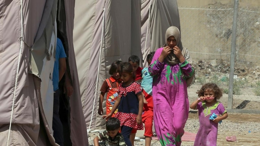 A displaced woman and children walk through rows of tents at a camp set up for people from Ramadi and the area in al-Shurta neighborhood of west Baghdad, Iraq, Thursday, April 30, 2015. There are 2.7 million people internally displaced in Iraq, where government forces are struggling to wrest back vast areas of the north and west seized by the Islamic State group last year. (AP Photo/Karim Kadim)
