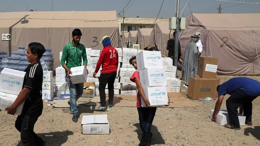 Displaced Iraqis receive humanitarian aid from UNICEF at a camp set up for people from Ramadi and the area in al-Shurta neighborhood of west Baghdad, Iraq, Thursday, April 30, 2015. The head of the European Union's humanitarian aid department has warned that the situation in Iraq is rapidly deteriorating while the world is preoccupied with crises elsewhere. (AP Photo/Karim Kadim)