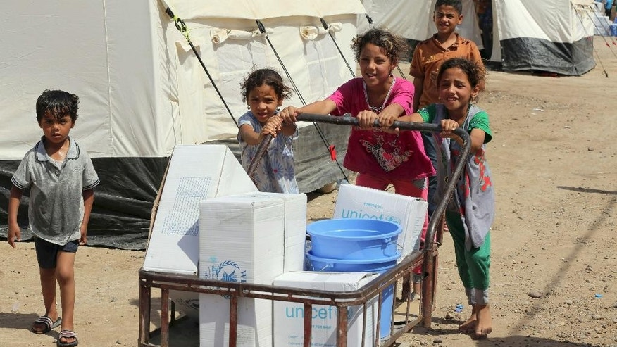 Displaced children push a cart with humanitarian aid that they received from UNICEF at a camp set up for people from Ramadi and the area in al-Shurta neighborhood of west Baghdad, Iraq, Thursday, April 30, 2015. Jean-Louis de Brouwer, the head of the European Union's humanitarian aid department, has warned that the situation in Iraq is rapidly deteriorating while the world is preoccupied with crises elsewhere. (AP Photo/Karim Kadim)