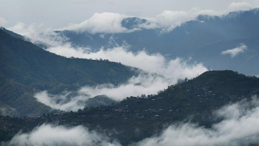 In this April 28, 2015, file photo, low-lying clouds are seen in the valleys below Paslang village near the epicenter of Saturday's massive earthquake in the Gorkha district of Nepal. Even amid the misery, with no running water, no electricity, and anger and frustration boiling over it's still possible to find examples of the picture postcard image of Nepal many foreigners hold in their imaginations. People here have long seen their struggles with poverty, corruption and infrastructure failures, and with a political fecklessness almost Shakespearean in scale, overshadowed by the beauty of the land and its firm place in the collective popular romantic imagination. (AP Photo/Wally Santana, File)
