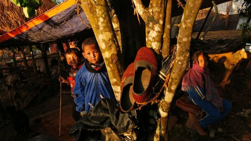 In this April 28, 2015, file photo, children peer out of makeshift shelter in destroyed village of Paslang near the epicenter of Saturday's massive earthquake in the Gorkha District of Nepal. Even amid the misery, with no running water, no electricity, and anger and frustration boiling over it's still possible to find examples of the picture postcard image of Nepal many foreigners hold in their imaginations. People here have long seen their struggles with poverty, corruption and infrastructure failures, and with a political fecklessness almost Shakespearean in scale, overshadowed by the beauty of the land and its firm place in the collective popular romantic imagination. (AP Photo/Wally Santana, File)