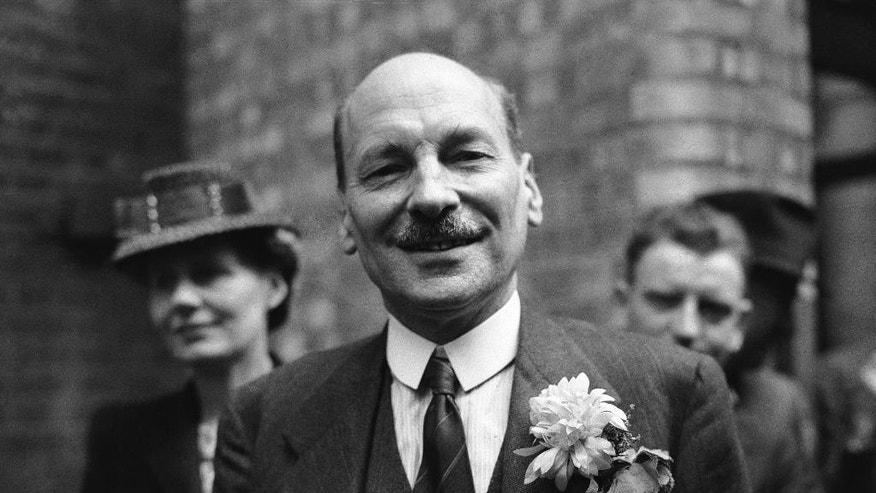 FILE - This is a July 26, 1945  file photo of Labour Party leader Clement Attlee as he smiles at the cheering throngs which gathered at Transport House, in London to celebrate Labour's election victory. Even though Winston Churchill triumphantly led the country through World War II, his Conservative Party would suffer a stunning defeat in the 1945 general election. Attlee's Labour Party won by a landslide and would become one of the most transformative governments of the 20th century, notably with the creation of the National Health Service. (AP Photo/Leslie Priest, File)