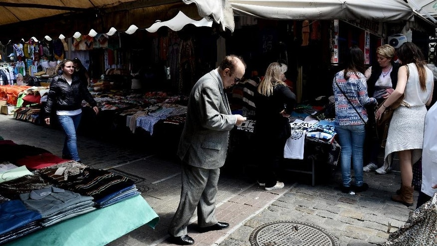 People shop at a flea market at the northern port city of Thessaloniki, Greece, Wednesday, April 29, 2015. Greece says it will discuss with its creditors on Thursday a draft bill of reforms it hopes will earn their approval and pave the way for the unlocking of vitally needed bailout funds.  (AP Photo/Giannis Papanikos)