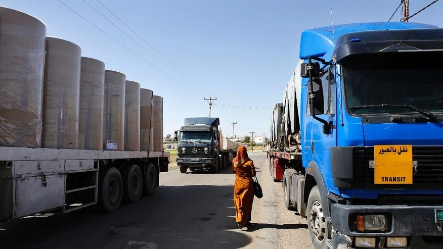 In this picture taken on Sunday, April 26, 2015, a woman walks through lines of trailer trucks sitting idle at the Jaber border crossing between Jordan and Syria north of Mafraq.  Jordan's overland trade has largely been paralyzed by recent border attacks from insurgents in neighboring Syria and Iraq. The violence has forced the closure of the only Syrian-Jordan trade crossing and further disrupted already sharply diminished cargo shipments between Jordan and Iraq.  (AP Photo/Raad Adayleh)