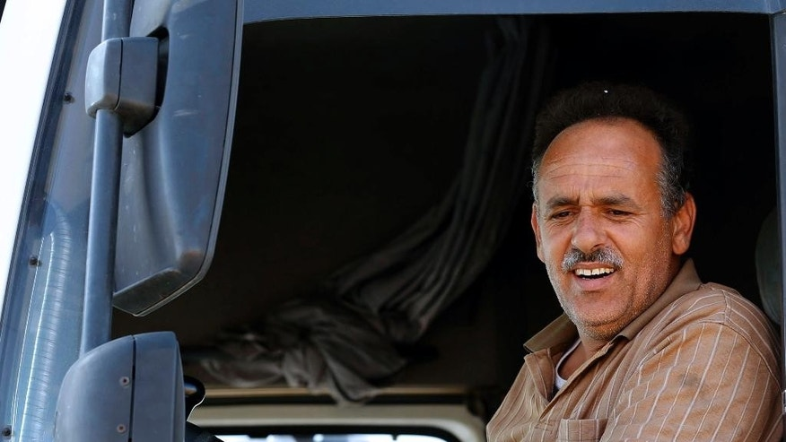 "In this Sunday, April 26, 2015, photo, Jordanian trucker Firas Zoabi, 39, drives out of a free trade zone next to the closed Syrian-Jordanian cargo crossing in Mafraq, Jordan. ""Iraq is closed, Syria is closed, only the (route to the) Gulf is left,"" said Zoabi, who has lost most of his business in recent weeks because of blocked or treacherous crossings. (AP Photo/Raad Adayleh)"