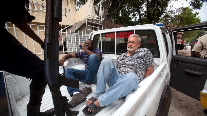 FILE - In this Friday, Sept. 5, 2014, file photo, U.S. citizen Michael Karl Geilenfeld waits in handcuffs as the manager of his orphanage sits with him in the back of a police truck outside the St. Joseph's Home For Boys after police closed it down in the Delmas area of Port-au-Prince, Haiti. A judge in Haiti has dismissed on Thursday, April 30, 2015, the case against a Geilenfeld who was accused of abusing residents of an orphanage he has run for three decades in the Haitian capital. (AP Photo/Dieu Nalio Chery, File)