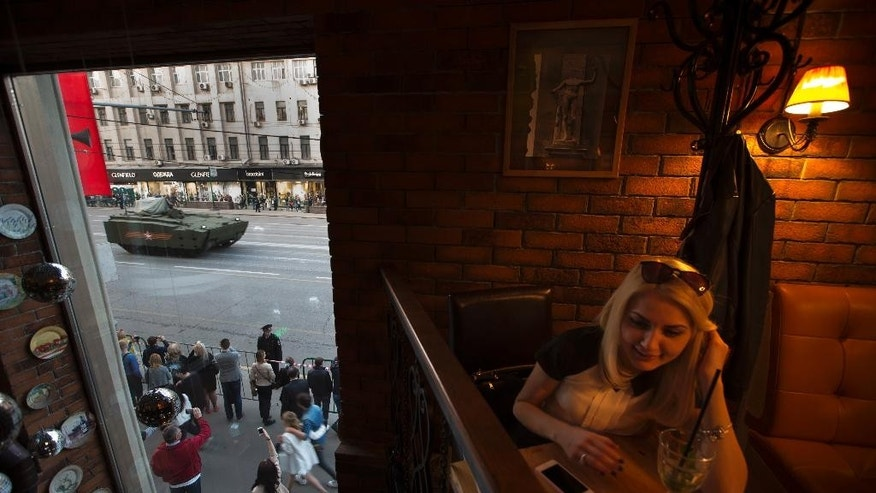 A woman sits in a cafe as new Russian military vehicles make their way to Red Square during a rehearsal for the Victory Day military parade which will take place at Moscow's Red Square on May 9 to celebrate 70 years after the victory in WWII, in Moscow, Russia, Wednesday, April 29, 2015. (AP Photo/Alexander Zemlianichenko)