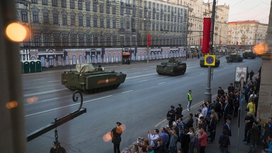 New Russian military vehicles making their way to Red Square are photographed through a cafe window during a rehearsal for the Victory Day military parade which will take place at Moscow's Red Square on May 9 to celebrate 70 years after the victory in WWII, in Moscow, Russia, Wednesday, April 29, 2015. (AP Photo/Alexander Zemlianichenko)