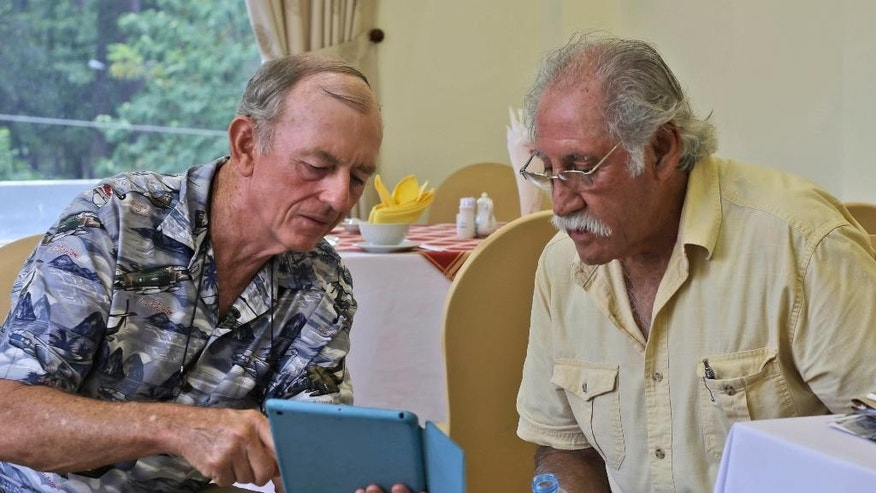 In this Tuesday, April 28, 2015 photo, former U.S. Marines Sgt. Kevin Maloney, left, of Hollywood, Florida and Master Gunnery Sgt. Juan Valdez, of Oceanside, California, look at photos on Maloney's tablet in Ho Chi Minh City, Vietnam. On the 40th anniversary of the fall of Saigon, 13 Marines returned to dedicate a plaque to their two fallen brothers at the site of the old embassy, which is now the U.S. Consulate. (AP Photo/Dita Alangkara)