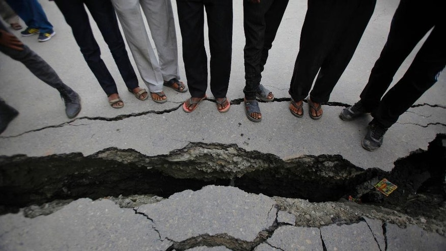 In this April 26, 2015 file photo, Nepalese people look at a cracked road after an earthquake in Kathmandu, Nepal. In mere seconds a powerful earthquake flattened a swathe of Nepal. Rebuilding the impoverished Himalayan nation's fragile economy will require a long slog, financed by foreign aid and money from its army of overseas workers.(AP Photo/Niranjan Shrestha, File)