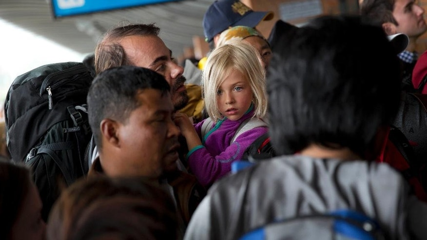 In this April 26, 2015 file photo, a German national girl and a man wait in a queue to go inside the Kathmandu international airport, in Kathmandu, Nepal. In mere seconds a powerful earthquake flattened a swathe of Nepal. The tourism industry, a pillar of the economy, has been shattered and it's unclear when the travelers will return.(AP Photo/Bernat Armangue, File)