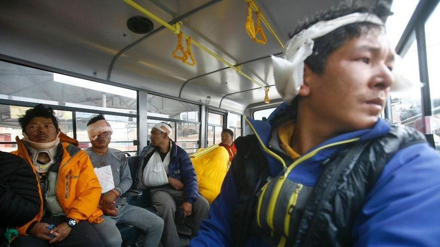 FILE – In this Sunday, April 26, 2015 file photo, Sherpa guides injured in an avalanche sit inside a bus after they were evacuated from Mount Everest Base Camp, in Kathmandu, Nepal. Despite a massive 7.8 magnitude earthquake that triggered a landslide that killed more than a dozen people, mostly Sherpa guides, at Everest base camp, government and trekking officials in Nepal said Thursday that expeditions to summit Mt. Everest may resume if climbers decide to go ahead. (AP Photo/Bikram Rai, File)