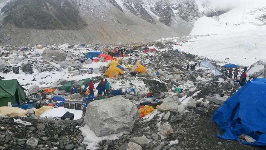 FILE – In this Tuesday, April 28, 2015 file photo, mountain guides and climbers stand beside camping and climbing gear piled up after an avalanche hit the area, at Everest Base Camp, Nepal. Despite a massive 7.8 magnitude earthquake that triggered a landslide that killed more than a dozen people, mostly Sherpa guides, at Everest base camp, government and trekking officials in Nepal said Thursday that expeditions to summit Mt. Everest may resume if climbers decide to go ahead. (AP Photo/Nima Namgyal Sherpa, File)