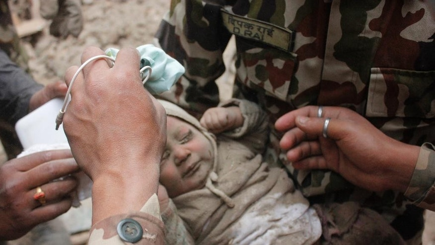 "In this Sunday, April 26, 2015, photo taken by Amul Thapasaw and provided by Kathmandu Today, four-month-old baby boy Sonit Awal is held up by Nepalese Army soldiers after being rescued from the rubble of his house in Bhaktapur, Nepal, after Saturday's 7.8-magnitude earthquake shook the densely populated Kathmandu valley.  Thapasaw says that when he saw the baby alive after 20 hours of rescue efforts ""… all my sorrow went. Everyone was clapping. It gave me energy and made me smile in spite of lots of pain hidden inside me."" (Amul Thapa/Kathmandu Today via AP)"