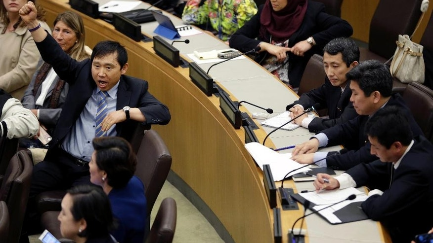 A North Korean defector, left, yells to try and drown out a statement being read by North Korean diplomats, right, during a panel on North Korean human rights abuses, at United Nations headquarters, Thursday, April 30, 2015. (AP Photo/Seth Wenig)