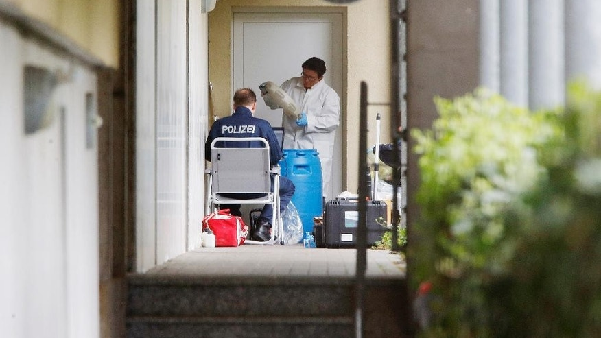 German police officers secure evidence in front of an apartment in Oberursel, Germany, Thursday, April 30, 2015.  Police have conducted an anti-terror raid in the city near Frankfurt and taken a man and a woman into custody.  (AP Photo/Michael Probst)