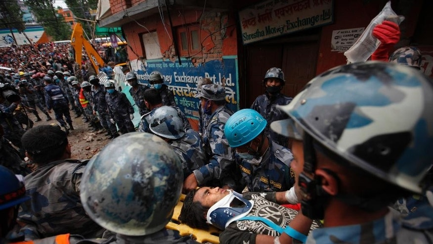 A Nepalese teenage boy is rushed to hospital on a stretcher after being rescued by Nepalese policemen and US rescuers alive from the debris of a building five days after the earthquake in Kathmandu, Nepal, Thursday, April 30, 2015. (AP Photo / Niranjan Shrestha)
