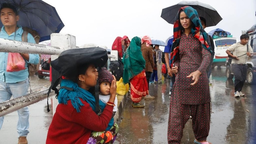 A Nepalese woman protects her child from rain as she waits for transport to go to her home town, in Kathmandu, Nepal, Thursday, April 30, 2015. The 7.8-magnitude earthquake shook Nepal's capital and the densely populated Kathmandu valley on Saturday devastating the region and leaving tens of thousands shell-shocked and sleeping in streets. (AP Photo/Manish Swarup)