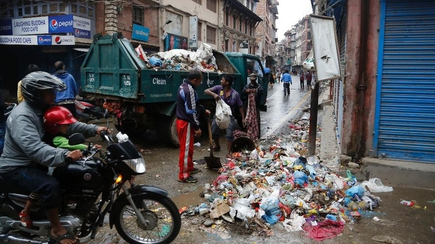 Kathmandu municipal workers collect garbage from the city in Kathmandu, Nepal, Thursday, April 30, 2015. The 7.8-magnitude earthquake shook Nepal's capital and the densely populated Kathmandu valley on Saturday devastating the region and leaving tens of thousands shell-shocked and sleeping in streets. (AP Photo/Manish Swarup)