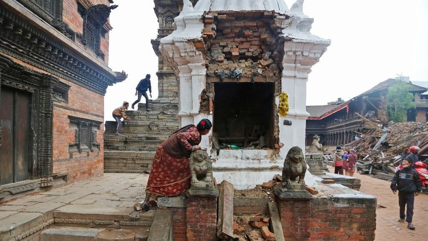 A Nepalese woman looks inside a damaged temple and prays in Bhaktapur near Kathmandu, Nepal, Thursday, April 30, 2015. The 7.8-magnitude earthquake shook Nepal's capital and the densely populated Kathmandu valley on Saturday devastating the region and leaving tens of thousands shell-shocked and sleeping in streets. (AP Photo/Manish Swarup)