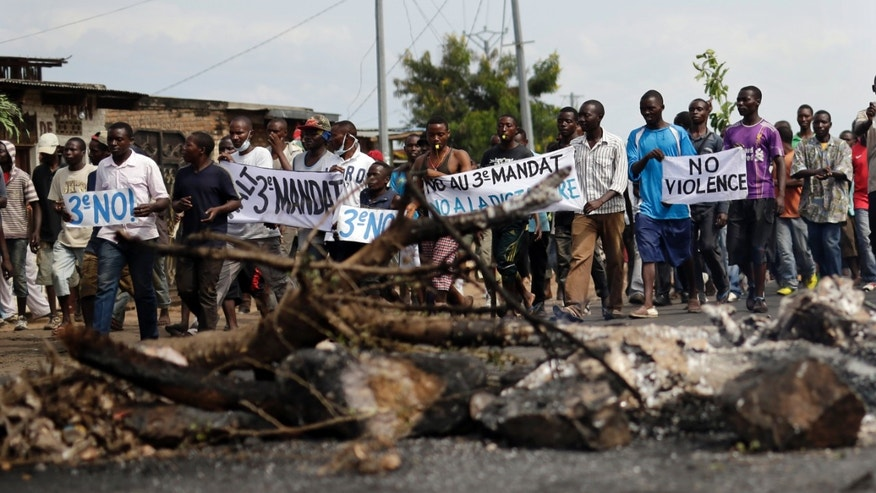 May 1, 2015 - Demonstrators walk over a street barricade in the Musaga neighborhood of Bujumbura, Burundi. Anti-government street demonstrations continued for a 6th day in protest against the move by President Pierre Nkurunziza to seek a third term in office.