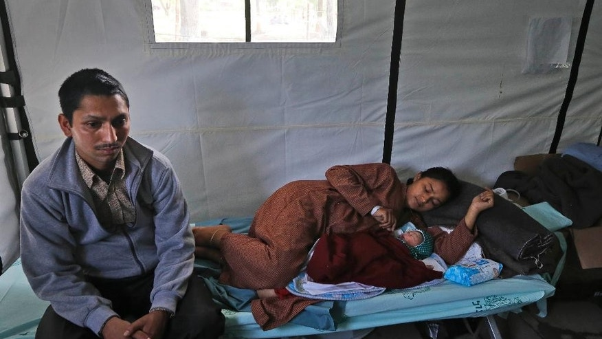 Nepalese woman Lata Chand,19, looks at her newly born baby girl as her husband Hariender Chand, 25, sits beside them at the Israeli field hospital in Kathmandu, Nepal, Friday, May 1, 2015. (AP Photo / Manish Swarup)