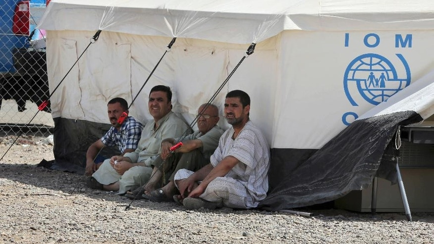 Men sit in the shade of a tent at a camp set up for people from Ramadi and around the area in al-Shurta neighborhood of west Baghdad, Iraq, Thursday, April 30, 2015. There are 2.7 million people internally displaced in Iraq, where government forces are struggling to wrest back vast areas of the north and west seized by the Islamic State group last year. (AP Photo/Karim Kadim)