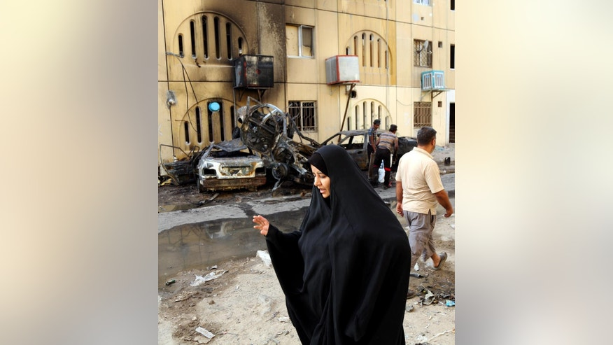A woman walks past the site of a car bomb attack in the Shiite district of Talibiyah in Baghdad, Iraq, Friday, May 1, 2015. A string of car bomb attacks across the Iraqi capital targeted mostly Shiite districts.(AP Photo/Karim Kadim)