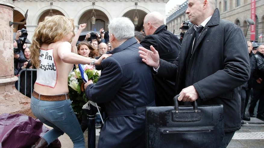 "Femen activist with ""Le Pen Top Fascist"" painted on her body appears as France's far-right National Front president Marine Le Pen places a wreath at Joan of Arc statue during its annual May Day march, in Paris, France, Friday, May 1, 2015. France's far-right National Front is holding its annual May Day march, but for the first time the party's founder Jean-Marie Le Pen _ on the outs with his daughter who presides over the party _is not taking a seat at the tribune. (AP Photo/Francois Mori)"