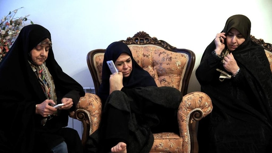 In this picture taken on Saturday, Jan. 31, 2015, Zohreh Etezadossaltaneh, center, talks on her mobile phone, held with her foot, during a meeting at her friend's home in Tehran, Iran. Now 52 years old, the retired Iranian teacher who was born without arms has dedicated herself to helping others with similar disabilities live full and satisfying lives.(AP Photo/Ebrahim Noroozi)