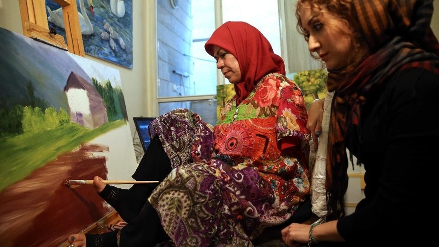 """In this picture taken on Wednesday, Jan. 28, 2015, Zohreh Etezadossaltaneh, left, who was born without arms, paints as her teacher Parisa Samavatian observes, at her home in Tehran, Iran. """"She works so easily that I've totally forgotten she paints with her feet,"""" said Samavatian.(AP Photo/Ebrahim Noroozi)"""