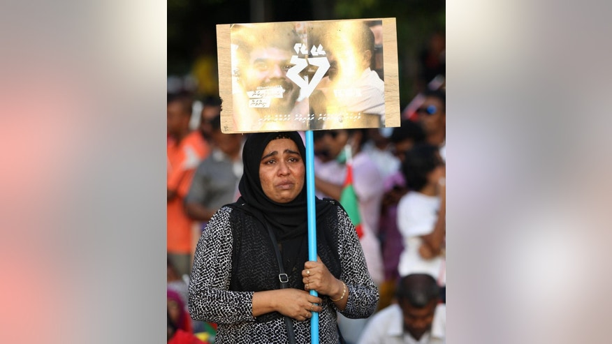 An opposition supporter holds a placard and cries during a protest demanding Maldives President Yameen Abdul Gayoom resign and jailed ex-president Mohamed Nasheed be freed, in Male', Maldives, Friday, May 1, 2015. The thousands of protesters marching in one of the biggest marches in Male accused Gayoom of jailing Nasheed and others who he sees as political threats. (AP Photo/Sinan Hussain)